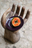 Papaya hand, skiva, tropisk frukt, hav, sand Royaltyfria Foton
