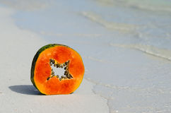 Papaya hand, skiva, tropisk frukt, hav, sand Royaltyfri Fotografi