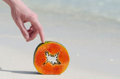 Papaya, hand, slice, tropical fruit, sea, sand Stock Images