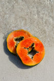 Papaya, hand, slice, tropical fruit, sea, sand Royalty Free Stock Photography