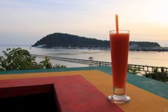 The papaya juce with view on the sunset beach. Royalty Free Stock Photos