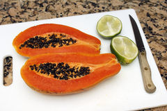 Papaya and Lime. One large dark orange papaya fruit cut in half lengthwise with black seeds inside next to two halves of a lime on a white cutting board near a stock photos