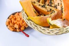 Papaya madura en cesta de fruta del bastón en el fondo blanco fotos de archivo