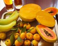 Papaya mango, banan och och mandarned över en metallisk silver Arkivfoto