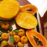Papaya mango, banan och och mandarned över en metallisk silver Royaltyfri Bild