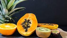 Papaya, naranja, mitades del kiwi, soporte de piedra del tablero con un marco de madera fotografía de archivo