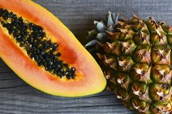 Papaya and pineapple tropical fruits cut in half on old wooden table.Healthy raw food,diet or vegan meal concept. Selective focus Royalty Free Stock Image