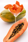 Papaya - a popular breakfast fruit. The oblong shape of half a papaya and its fruit flesh in a glass. The depth of field is running across both the papaya slices Stock Images