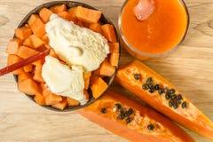 Papaya, Saft und Eiscreme für Wüste auf hölzernem Hintergrund Lizenzfreie Stockbilder