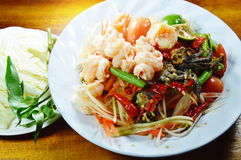 Papaya salad called Som tum in Thai eat couple with fresh vegetable on table. Papaya salad called Som tum in Thai eat couple with fresh vegetable on wood table Royalty Free Stock Photos