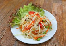 Papaya salad with crab in white plate on wood table royalty free stock photography