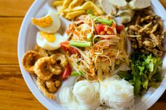 Papaya salad food selection. Fresh prepared asian SomTam papaya salad selection served with glass noodle,egg, pork cracklings, bamboo shots, fish, sausage and royalty free stock image