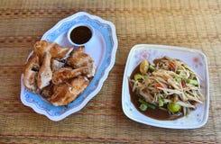 Papaya salad and Grilled Chicken. Thai papaya spicy salad or know as Som Tum and Grilled Chicken with sauce Stock Image