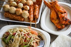 Papaya salad grilled chicken wing and meat ball with sticky rice served on plate Thai style food stock images