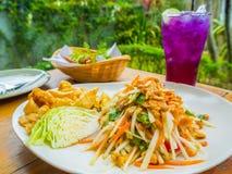 Papaya salad and ice crake lemon tea. Thai food culture. Papaya salad or what we called Somtum and ice crake lemon tea on wooden table in garden background of Royalty Free Stock Images