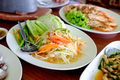 Papaya salad in plate and other food. On table Royalty Free Stock Image