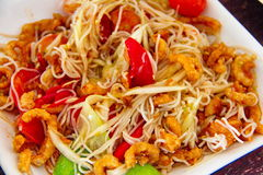 Papaya salad or Som Tum. With rice noodle and salted crab and fermented fish on white dish, spicy and  popular food of Thailand Royalty Free Stock Image