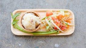Papaya salad (Som tum) with sticky rice. On wood tray royalty free stock image