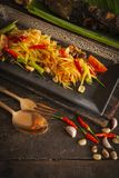 Papaya Salad Som tum Thai on square black plate placed on the wood table there are bean, grilled fish, garlic, chilli spoon and. Fork placed around close up stock images