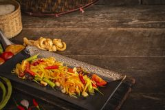 Papaya Salad Som tum Thai on square black plate placed on the wood table there are tomato, chilli, garlic, long bean, sticky. Rice and palm sugar placed around royalty free stock photos