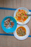 Papaya salad (som tum Thai) with sticky rice. Grilled beef and Spicy minced pork salad on mat stock photos