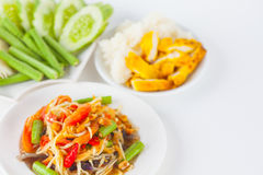 Papaya salad. (som tum Thai) with sticky rice and grilled chicken on white paper background royalty free stock photo