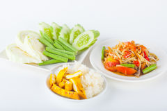 Papaya salad. (som tum Thai) with sticky rice and grilled chicken on white paper background stock image