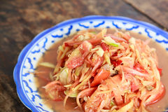Papaya salad Thai cuisine spicy delicious. With vegetables on wood background Royalty Free Stock Photography