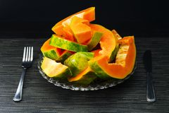 Papaya schnitt Stücke in der Platte mit Gabel und adelt auf schwarzem Hintergrund Lizenzfreie Stockbilder