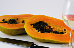 Papaya (series3). Isolated shot of a papaya being cut with a large knife and wine glass Royalty Free Stock Photography