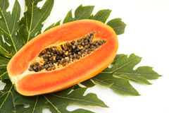 Papaya slice on green leaf. On white background. Stock Photos