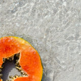 Papaya slice, slice, cut, tropic, fruit, sand water, square Royalty Free Stock Image