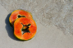 Papaya slice, slice, cut, tropic, fruit, sand water, square Royalty Free Stock Photo