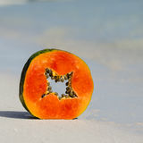 Papaya slice on the white sand and crystal water. Royalty Free Stock Image