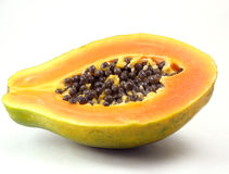 Papaya sliced in half on white. Green papaya with orange and yellow flesh and black seeds, cut in half on white background Royalty Free Stock Images