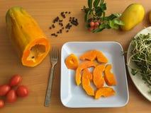 Papaya slices on plate, mango and tomatoes Royalty Free Stock Photo