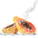 Papaya som faller i vatten Royaltyfria Bilder