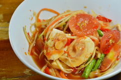 Papaya spicy salad or Som Tum in Thai topping salty egg on bowl. Papaya spicy salad or Som Tum in Thai topping salty egg on white bowl Stock Photos