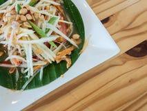 Papaya spicy salad Thai style called Somtum, famous traditional food. Papaya spicy salad Thai style called Som-Tum on banana leaf, famous traditional food stock photography