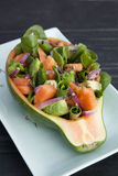 Papaya, Spinach & Avocado Salad. Served in a papaya shell with herb dressing and red onion on light blue plate Stock Photography