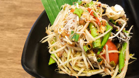 Papayasallad med vermiceller och den saltade krabban på svart maträtt royaltyfri bild