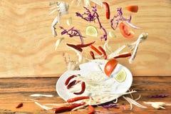 Papayasalladmeny som plaskar på träbakgrund, grönsaker som plaskar, thailändsk mat Royaltyfri Foto