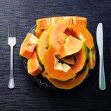 Papayasnittstycken i platta med gaffeln och riddare på svart bakgrund Papaya på den tjänade som plattan Royaltyfri Foto