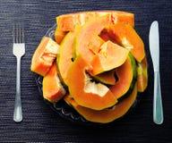 Papayasnittstycken i platta med gaffeln och riddare på svart bakgrund Vegetarisk frukost på bästa sikt för platta Royaltyfri Bild