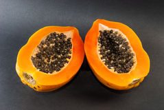 Papaye coupée dans la moitié sur le fond noir Images libres de droits