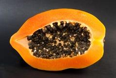 Papaye coupée dans la moitié sur le fond noir Image libre de droits