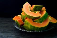 Papaye coupée sur le fond noir Coupez la papaye du plat servi au petit déjeuner végétarien Photos libres de droits