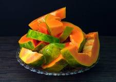 Papaye coupée sur le fond noir La papaye fraîche du plat a servi au petit déjeuner végétarien Photos libres de droits