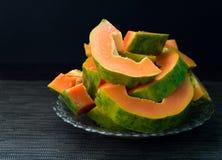 Papaye coupée sur le fond noir La papaye orange du plat a servi au petit déjeuner végétarien Photographie stock