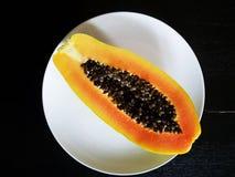 Papaye mûre coupée en tranches sur le fond noir Photo libre de droits